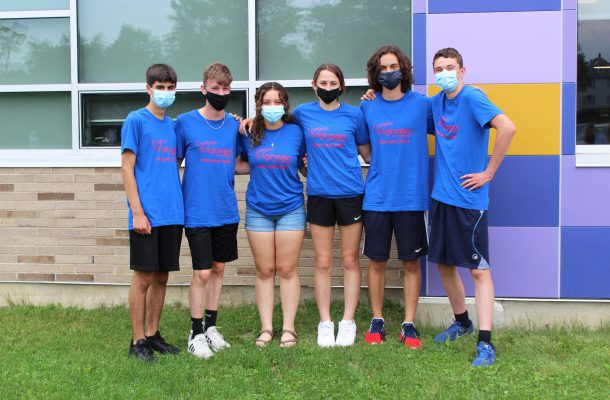 six teenaged teammates all wearing face masks and blue t-shirts pose outside the school, with gold and purple school colors in the background.