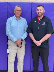 two gentlemen pose in front of a purple wall