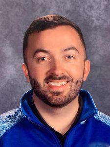 a young man with dark hair and dark facial hair wearing a blue zip up sweatshirt smiles at the camera