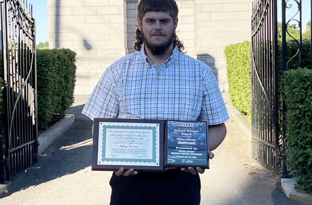 a young man holds two plaques