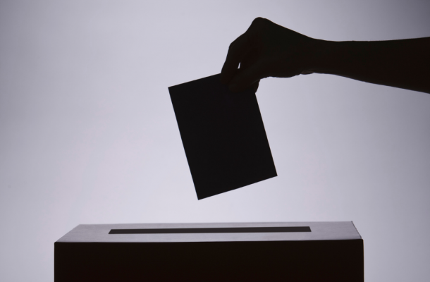 a shadowy figure drops a ballot into a voting box